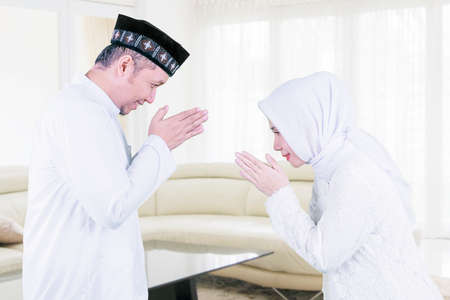 Muslim young man showing congratulate hands gesture Eid Mubarak to his wife in the living room. Shot at home