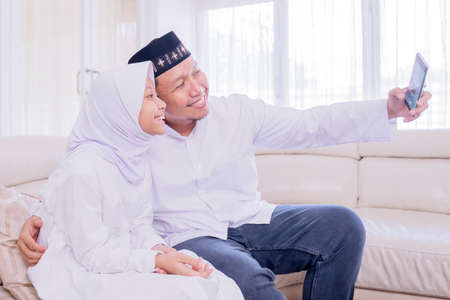 Muslim young man with his daughter taking selfie photo together by using a smartphone during Eid Mubarak in living room. Shot at home Zdjęcie Seryjne