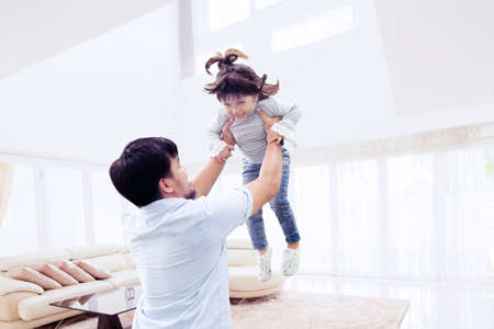 Picture of happy father lifting his daughter while having fun together in the living room. Shot at home