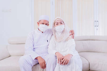 Happy Muslim old couple wearing face mask while looking at the camera and sitting together on the sofa at home Zdjęcie Seryjne