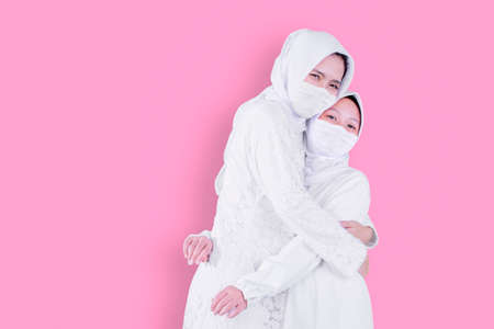 Muslim little girl wearing face mask while embracing her mother in the studio with pink background
