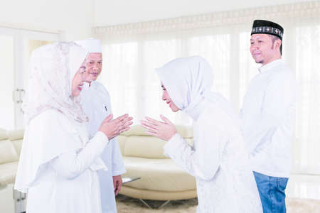 Muslim young woman apologizing to her parents during Eid Mubarak while standing with her husband in the living room at home