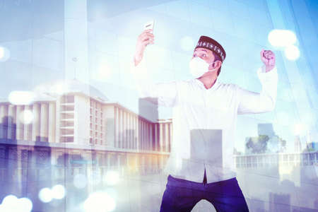 Double exposure of excited Muslim man reading good news on a cellphone while wearing face mask and standing with mosque background