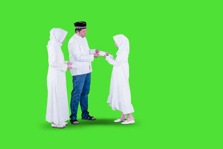 Happy Muslim parents giving money envelope to her daughter while standing in the studio during Eid Mubarak. Shot with green screen background