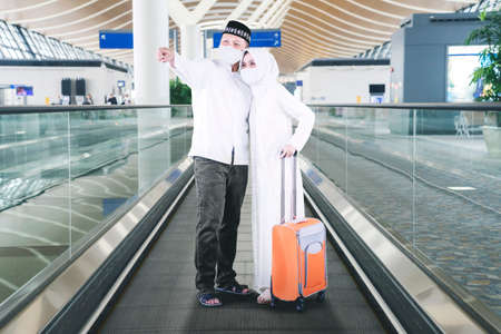 Muslim young couple wearing face mask while pointing to the flight information board and standing on escalator. Shot at airport terminal