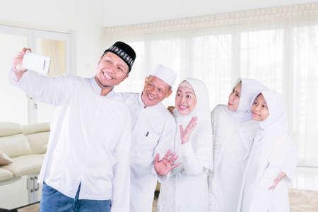 Three generation happy muslim family making video call in the living room during Eid Mubarak