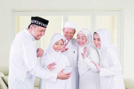 Three generation muslim family making video call in the living room during Eid Mubarak