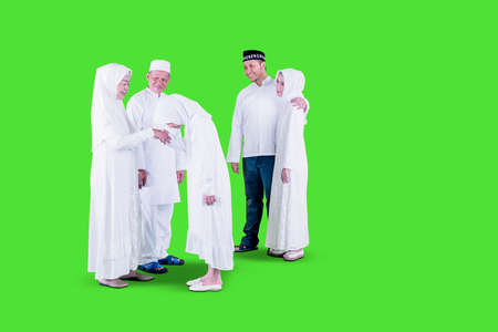 Muslim little girl apologizing to her grandparents and handshaking while standing with parents during Eid Mubarak in the studio with green screen background