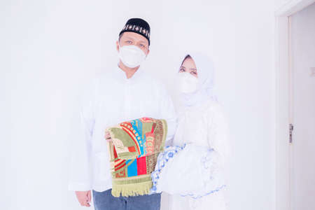 Muslim young couple wearing face mask while carrying prayer rugs during ready to congregation prays Zdjęcie Seryjne