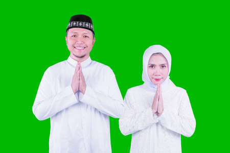 Happy Muslim young couple showing congratulate hands gesture Eid Mubarak while standing in the studio with green screen background