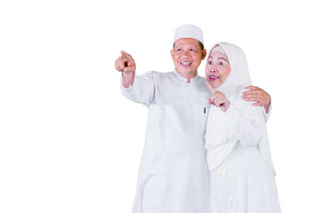 Happy Muslim old man embracing his wife while looking and pointing at copy space in the studio. Isolated on white background