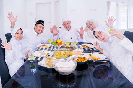 Three generation cheerful Muslim family waving hands at the camera while having dinner together during Eid Mubarak in dining room at home Zdjęcie Seryjne