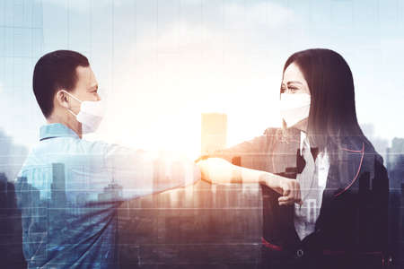 Double exposure of two business people wearing face mask while meeting and greeting with elbow in cityscape background Zdjęcie Seryjne