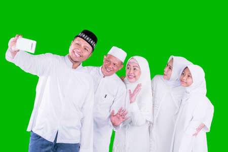 Three generation happy muslim family making video call in the studio while celebrating Eid Mubarak. Shot with green screen background