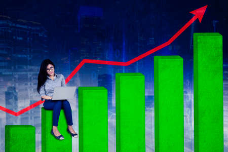 Businesswoman working with a laptop while sitting on growth graph with upward arrow in circuit board background Standard-Bild - 167156496