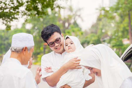 Three generation Muslim family looks happy while standing together during Eid Mubarak on the road