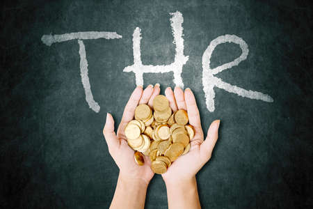 Close up of man hands holding heaped gold coins with THR word on blackboard background. Holiday allowances concept Foto de archivo