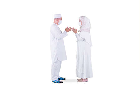 Full length of Muslim old couple handshaking and apologizing to each other during Eid Mubarak in the studio. Isolated on white background