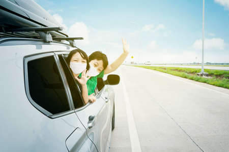 Happy siblings wearing face mask while waving hands during travel by car with blue sky background. Summer road trip concept