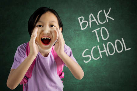 Picture of cute schoolgirl announces back to school by screaming in the classroom
