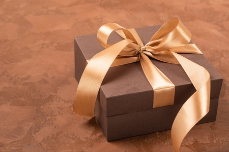 A gift in a paper box is decorated with a satin ribbon and a bow on a dark brown background. Flat layout. Copy space. Festive concept. Stok Fotoğraf