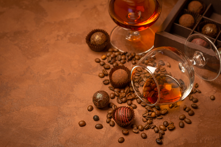 A glass of strong alcoholic drink brandy or brandy and candy of dark chocolate on a brown textured background. Copy space. Dark photo.