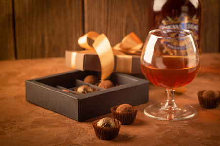 A glass of strong alcoholic drink brandy or brandy and a box of chocolates on a dark background. Selective focus. Copy space.