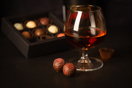 A glass of strong alcoholic drink brandy or brandy and candy made of Belgian chocolate on a dark background. Copy space.