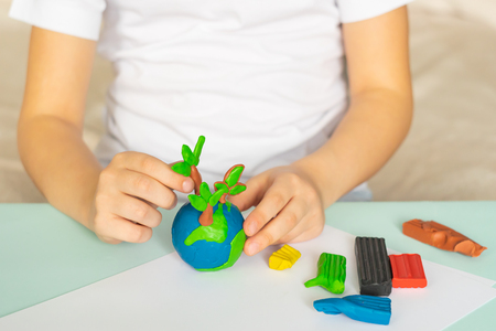 The child sculpts from plasticine the globe and trees. Layout of the planet in childrens palms. Concept ecology. Selective focus. Copy space