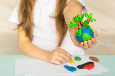 A small globe with trees in the hands of a child. Layout of the planet made of plasticine in children's palms. Concept ecology. Copy space. Horizontal frame. Stock fotó