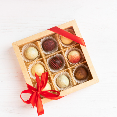 A gift set of various candies in a crafting box is decorated with a red satin ribbon. Festive concept. Flat layout. View from above