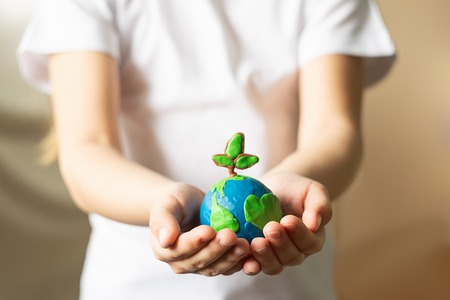 A small globe with trees in the hands of a child. Layout of the planet made of plasticine in childrens palms. Concept ecology. Copy space. Horizontal frame.