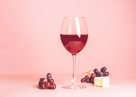 A glass with red wine and snack on a delicate pink background. Selective focus. Copy space. Minimalism Stock Photo