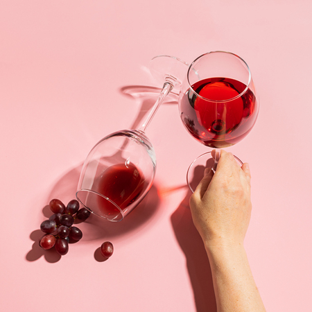 Female hand holding a glass with red wine and bunch of grapes on a gentle pink background. Selective focus. Minimalism.