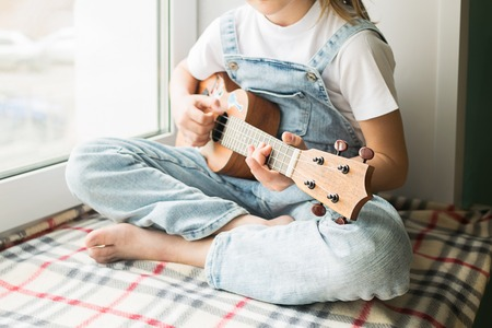 A little girl is sitting by the window in the house playing the guitar. Selective focus. The concept of music and art. 版權商用圖片