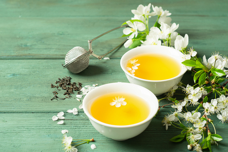 A cup of fragrant floral tea with petals in white forforkovy cups on a wooden background. Selective focus. Copy space.