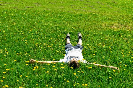 Teen boy lies on a green meadow in the fresh grass of the park. Summer concept, childrens games in the fresh air.