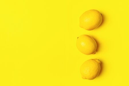 Fresh juicy lemon on a bright yellow background. Concept minimalism. Horizontal frame. Copy space. Flat Layout Top View Banco de Imagens