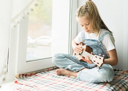 A little girl is sitting by the window in the house playing the guitar. Selective focus. The concept of music and art. Stock Photo