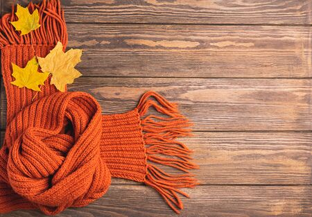 A bright knitted orange knitted scarf and maple leaf lies on a wooden background. Horizontal frame. Autumn concept