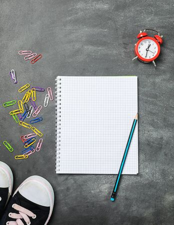 Educational supplies notebooks pens pencils sneakers alarm clock background of the chalk board. Concept back to school.