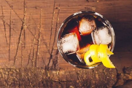 Strong alcoholic drink of brandy whiskey in a glass with ice cubes on a dark wooden background. Top view . Copy space. Stockfoto