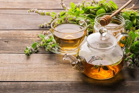 Tea with fresh leaves of lemon balm mint in a cup and teapot on a wooden rustic background. Healing herbal drink.