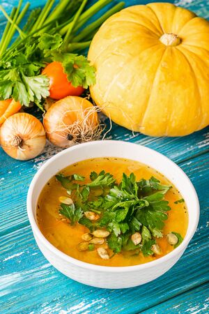 Pumpkin and fresh vegetables soup in white bowl close-up wooden blue background. Natural rustic style. Vertical frame. Imagens