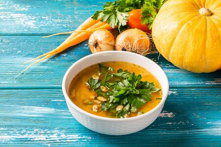 Pumpkin and fresh vegetables soup in white bowl close-up wooden blue background. Natural rustic style. Horizontal frame Imagens - 128891446