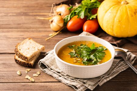 Pumpkin soup and fresh vegetables on a wooden background. Natural rustic style. Autumn concept Imagens