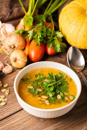 Pumpkin and fresh vegetables soup in white bowl wooden background. Natural rustic style. Vertical frame. Autumn concept.