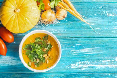 Pumpkin and fresh vegetables soup white bowl close-up wooden blue background. Natural rustic style. Top view flat lay.