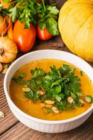 Pumpkin and fresh vegetables soup in white bowl wooden background. Natural rustic style. Vertical frame. Autumn concept. Imagens - 128891454