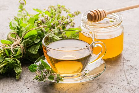 Cup of tea drink with fresh leaves of mint melissa and honey gray background. Healing herbal drink. Horizontal frame.